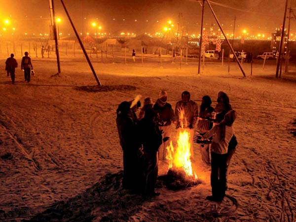 People warm themselves around a fire in Allahabad