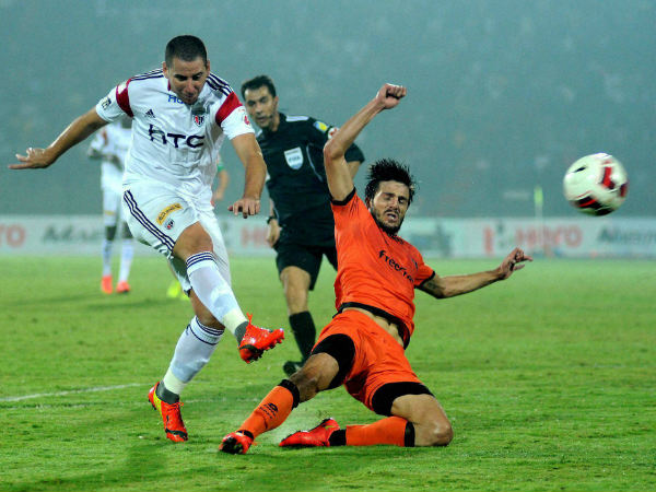Players of NorthEast United FC (in white) and Delhi Dynamos FC (in orange) in action during their ISL match, at Indira Gandhi Stadium in Guwahati on Monday.