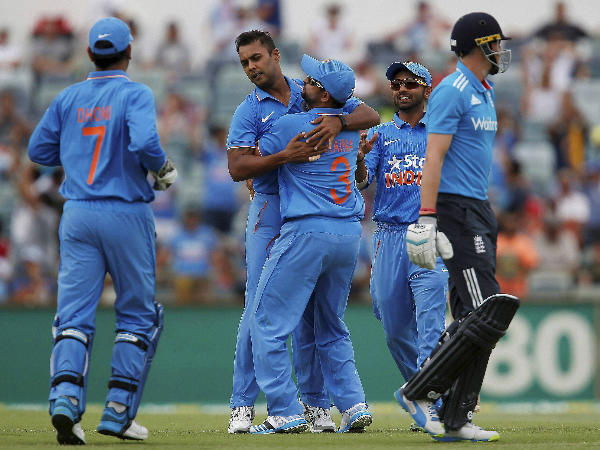 Stuart Binny, second left, is congratulated by teammates after taking the wicket of England's Joe Root, right