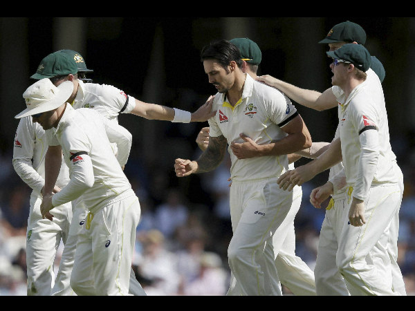 Mitchell Johnson, centre, celebrates taking the wicket of England's Joe Root on the third day