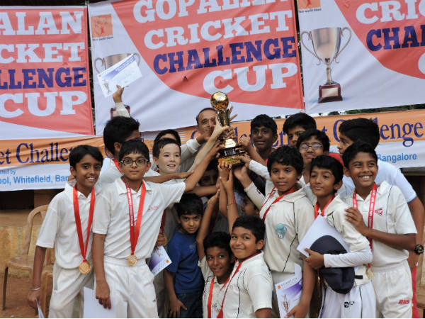 The victorious Mallya Aditi International School's players celebrate with the trophy. Samit (second left, front row) is also seen