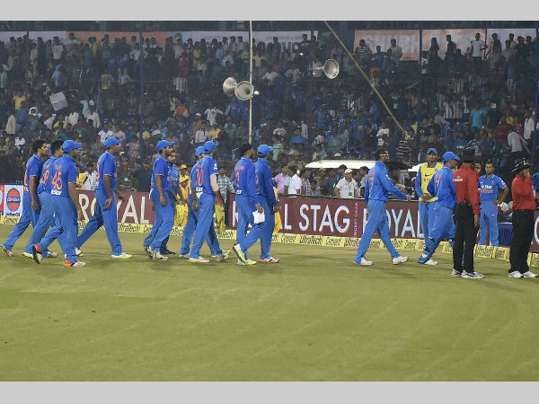 Indian players leave the ground after play was halted due to bottle-throwing by fans in Cuttack
