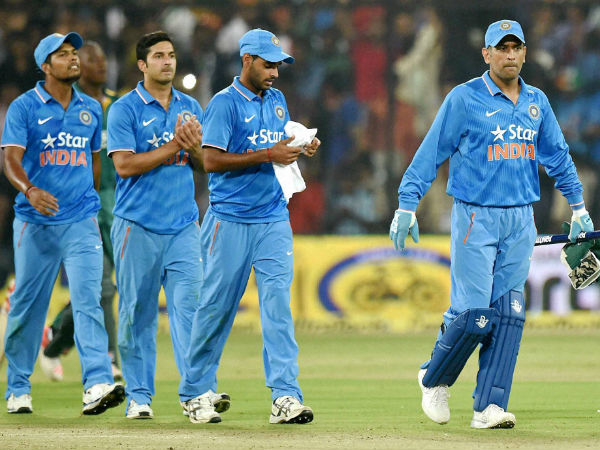 Dhoni (right) leads the team out of the ground after winning the 2nd ODI