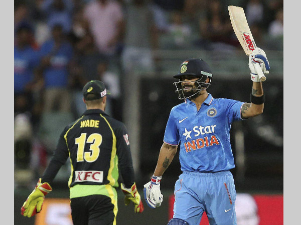 Virat Kohli raises his bat after completing 50 runs