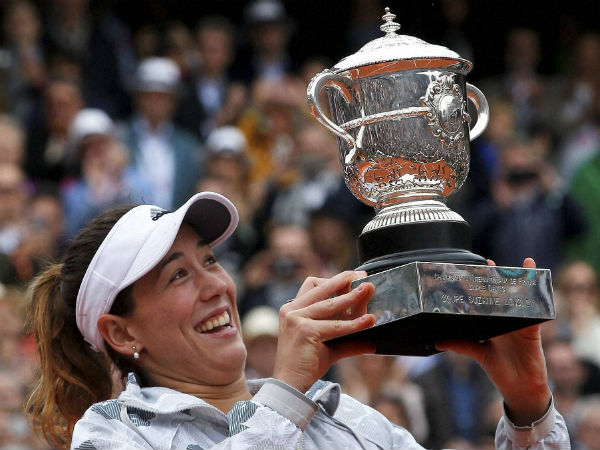 Spain's Garbine Muguruza holds the cup after defeating Serena Williams of the U.S. after their final match of the French Open tennis tournament at the Roland Garros stadium, Saturday, June 4.
