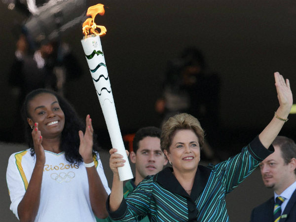 File photo: Brazil's President Dilma Rousseff holds the Olympic torch as Brazilian volleyball player Fabiana Claudino applauds after the torch was ignited at Planalto presidential palace in Brasilia, Brazil, Tuesday, May 3, 2016.
