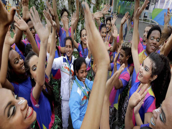 Indian field hockey players Deepika Deepika (center right) and Preety Dubey (center left) dance with performers after a welcome ceremony at the Olympic athletes village in Rio de Janeiro