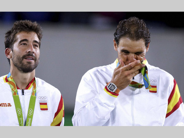 Rafael Nadal, right, kisses his gold medal while standing with partner Marc Lopez, after winning the men's doubles
