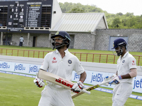 India's batsmen Shikhar Dhawan, left, and Lokesh Rahul walk to the pitch to start against West Indies on day one of their third cricket Test match.