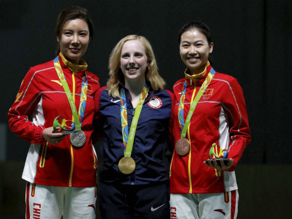 Gold medal winner, Virginia Thrasher, centre, poses for a picture with silver medal winner, Du li of China, left, and bronze medalist China's Yi Siling, during the victory ceremony for the Women's 10m Air Rifle event
