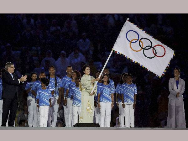 Tokyo Governor Yuriko Koike waves the Olympic flag as IOC President Thomas Bach stands at left during the closing ceremony in the Maracana stadium at the 2016 Summer Olympics in Rio de Janeiro, Brazil, on Aug. 21, 2016.