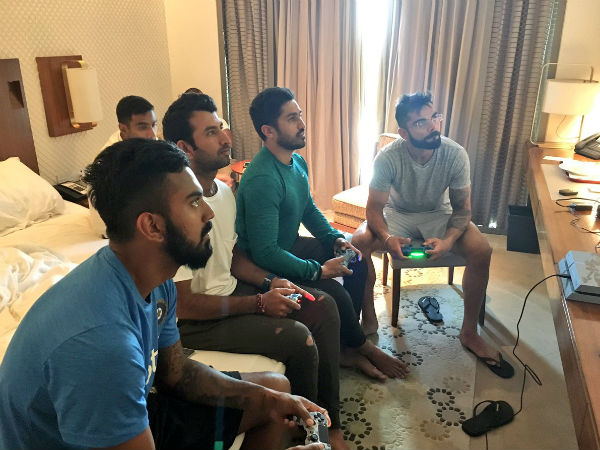 Cricketers playing video game at hotel