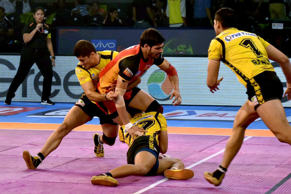 Players of Bengaluru Bulls (Red) and Telegu Titans (Yellow) in action during Pro Kabaddi league match at Tana Bhagat Indoor Stadium
