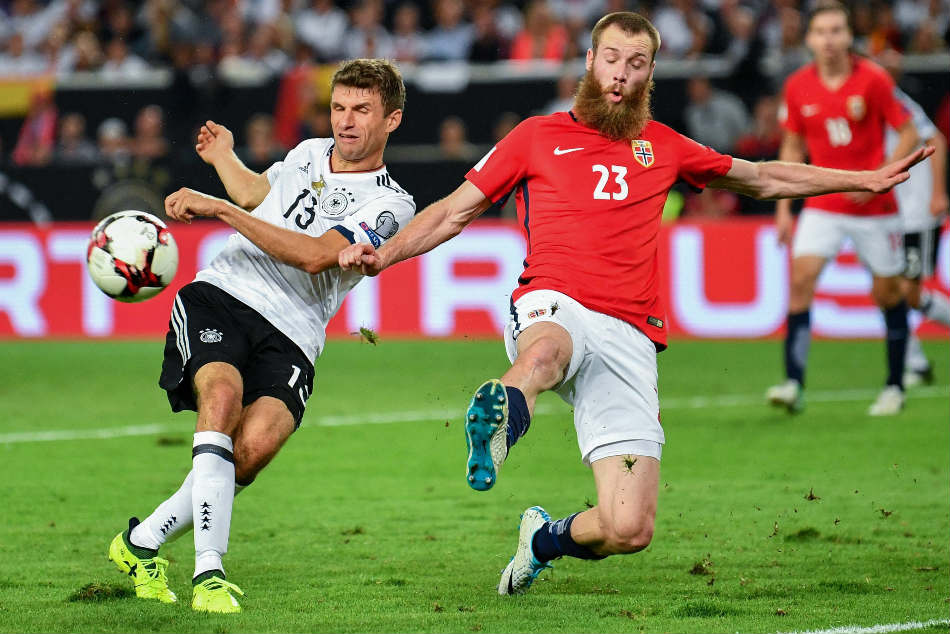 Germany's Thomas Mueller (L) and Norway's Jo Inge Berget vie for the ball during the World Cup qualification group stage match between Germany and Norway