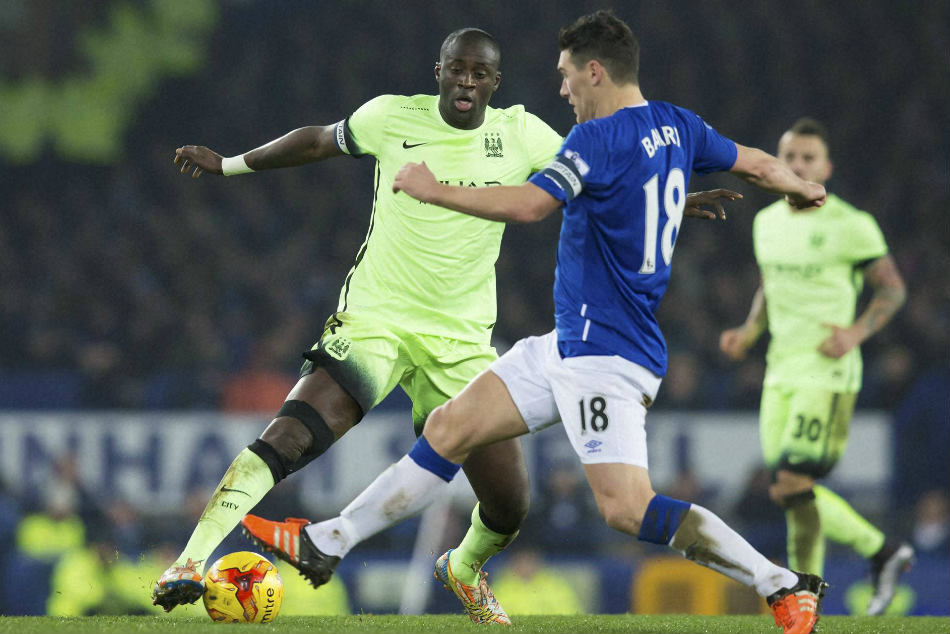 Manchester City's Yaya Toure (left) fights for the ball with Gareth Barry