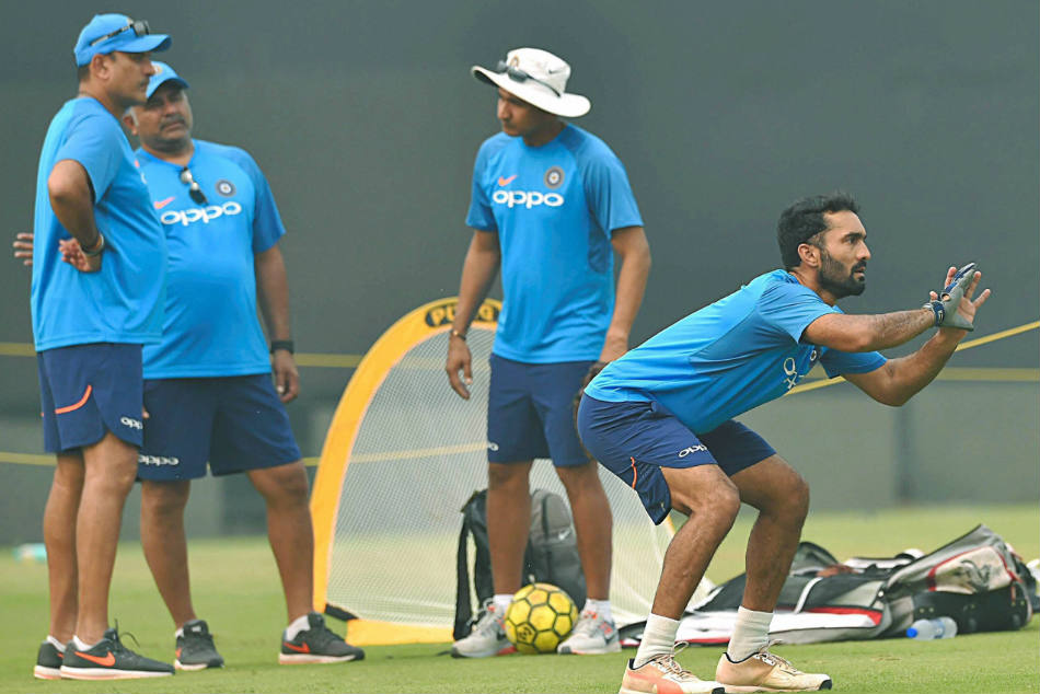Dinesh Karthik attends a training session as coach Ravi Shastri looks on.
