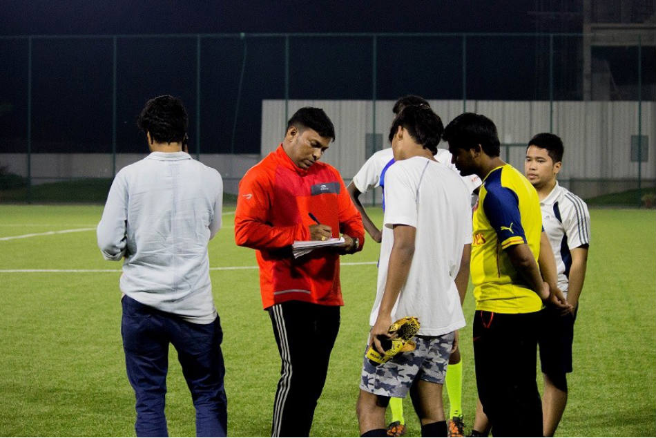FC Deccan coach Christopher Satish (centre) discusses tactics with his boys during a training session