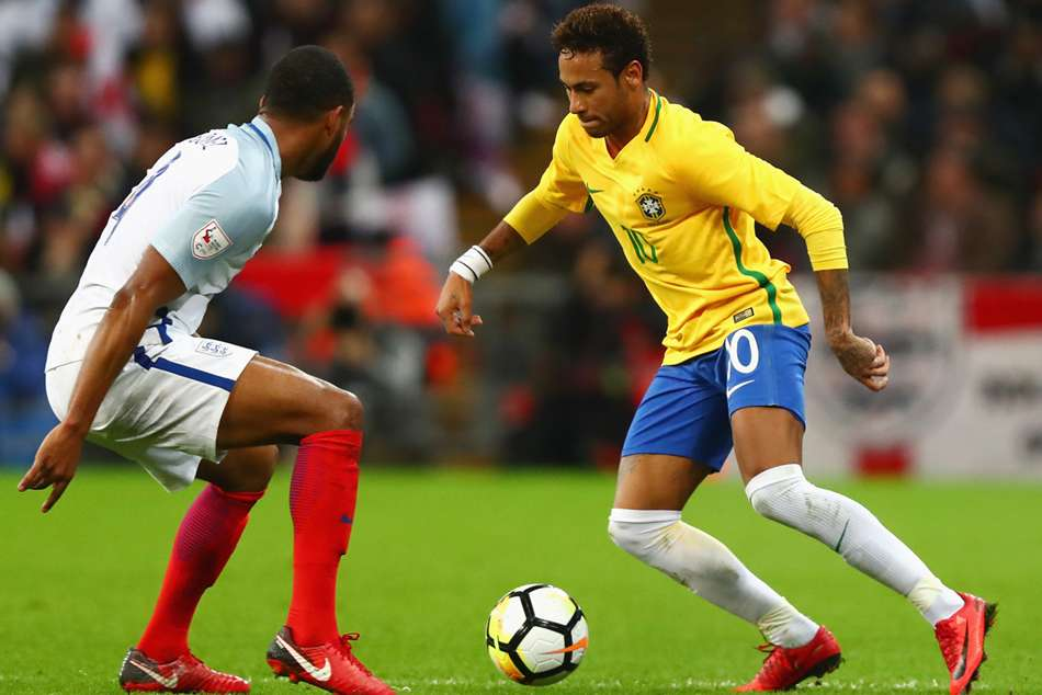 Brazil's Neymar (right) dribbles past England's Joe Gomez