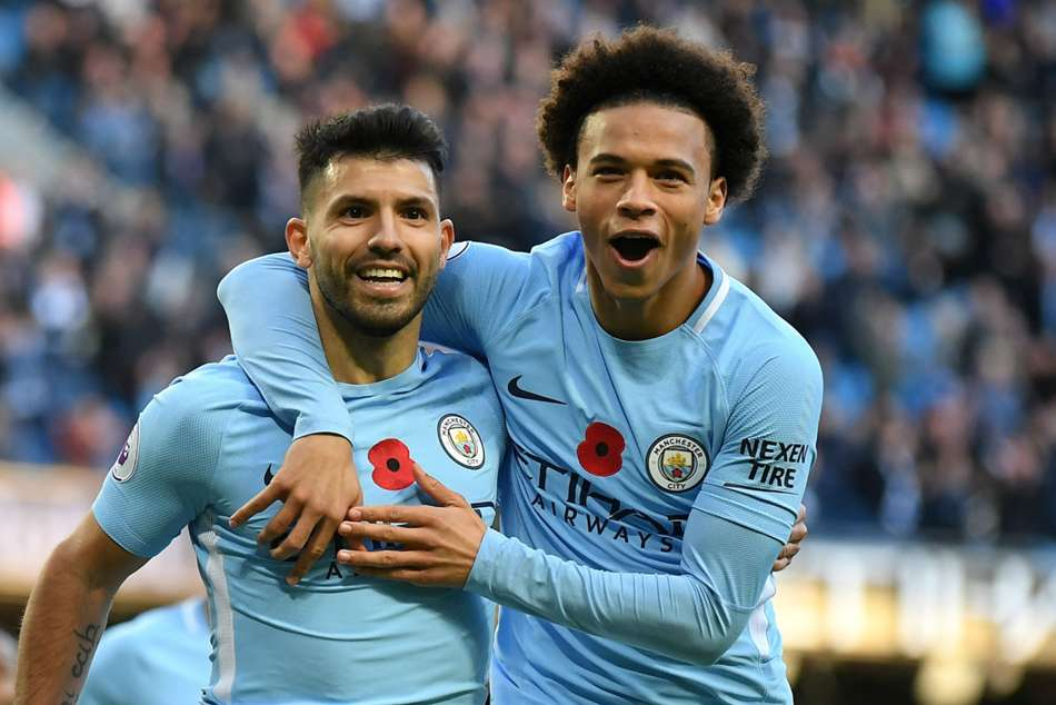Sergio Aguero of Man City (left) celebrates with teammate Leroy Sane after converting from the spot during their Premier League game against Arsenal at the Etihad Stadium on Sunday
