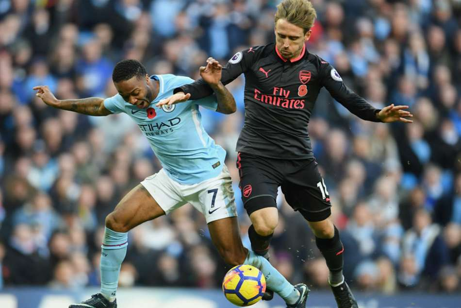 Sterling (left) of Man City went down after a challenge by Monreal of Arsenal