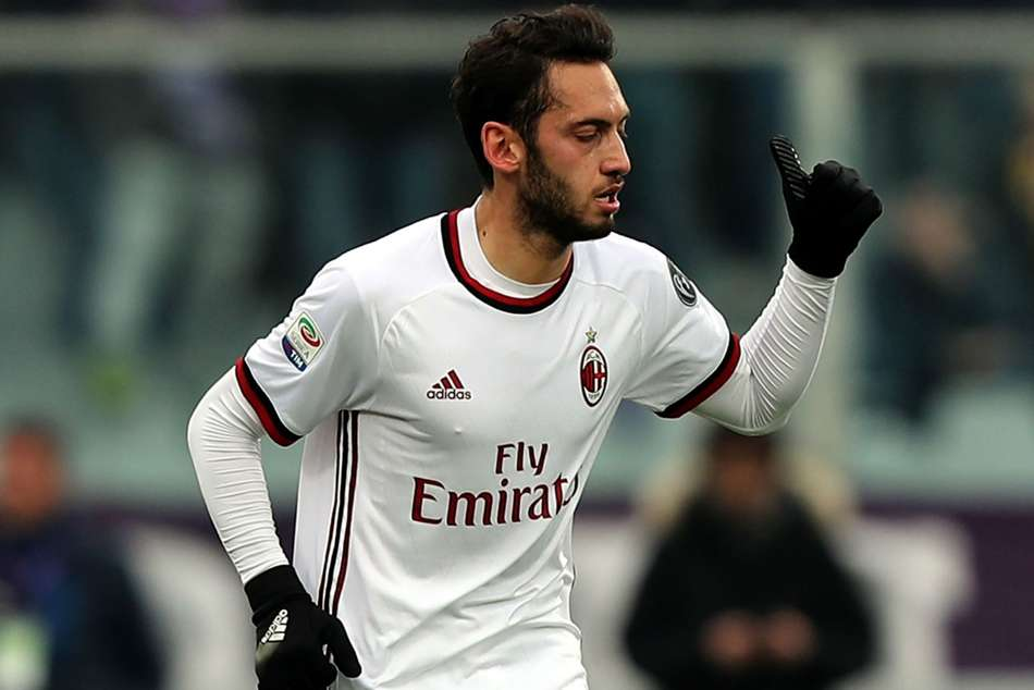 Hakan Calhanoglu celebrates after scoring the equaliser for AC Milan against Fiorentina