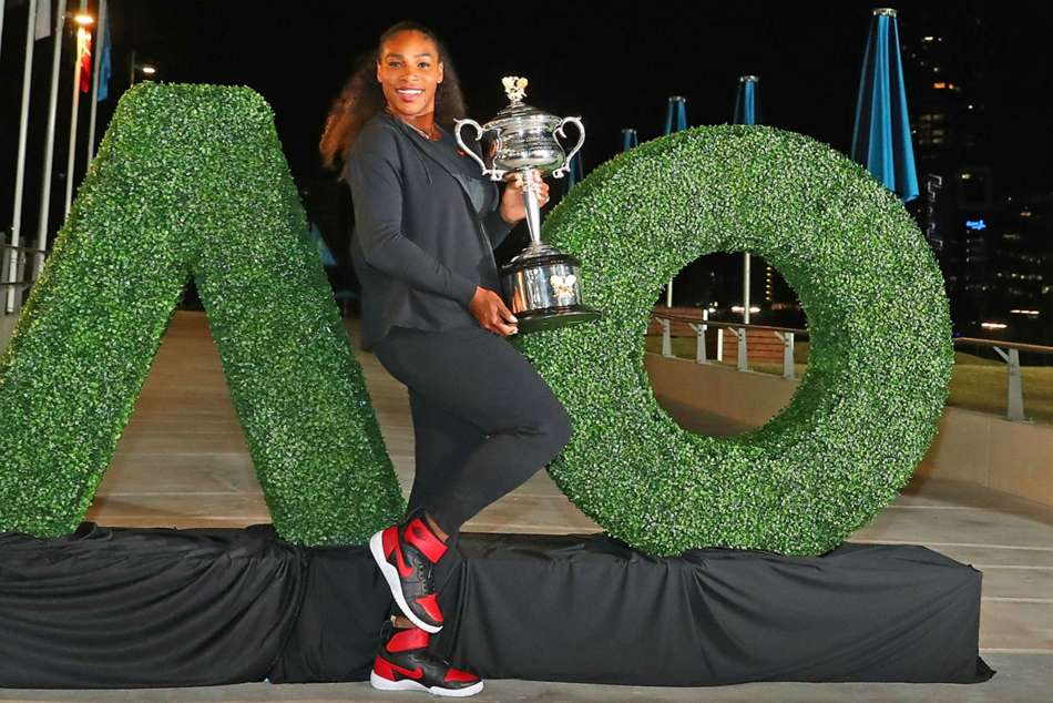 Serena Williams poses with Australian Open title she won earlier this year