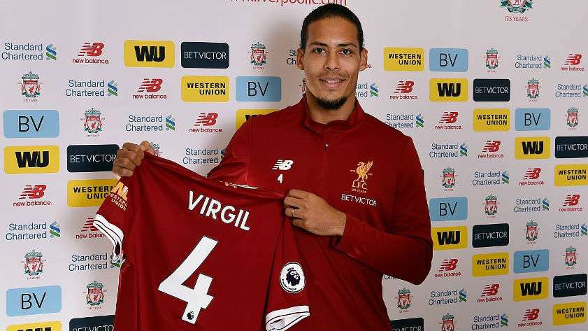 Virgil van Dijk poses with Liverpool shirt in hand after his record transfer from Southampton