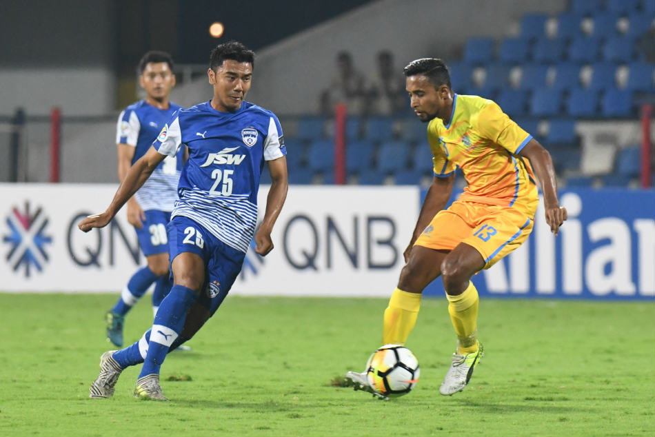 Bengaluru FC's Daniel Lalhlimpuia attempts to dribble past Atiqur Rahman of Abahani Dhaka during their AFC Cup match at the Sree Kanteerava Stadium on Wednesday