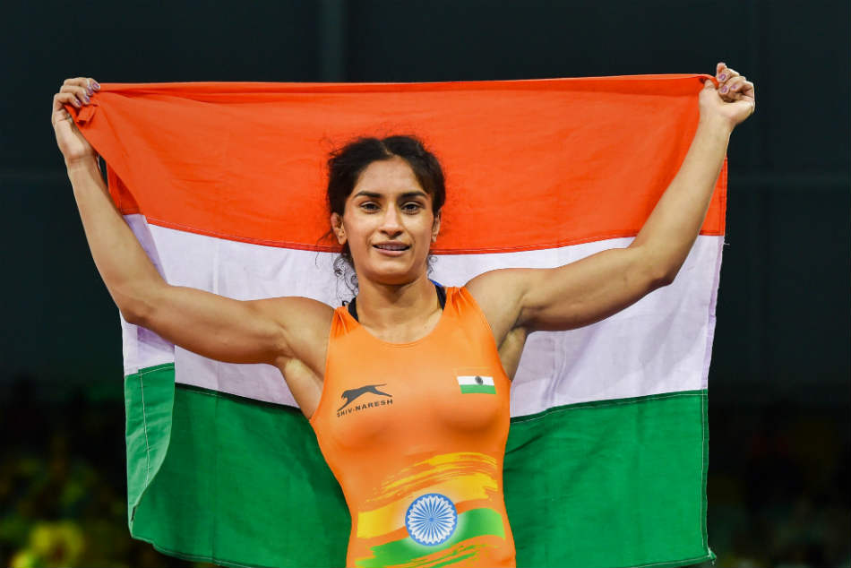 Indias wrestler Vinesh Phogat celebrates her gold winning effort in the 50kg freestyle event