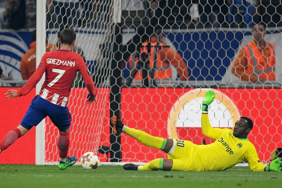 Atleticos Antoine Griezmann scores past compatriot and Marseilles Steven Mandanda