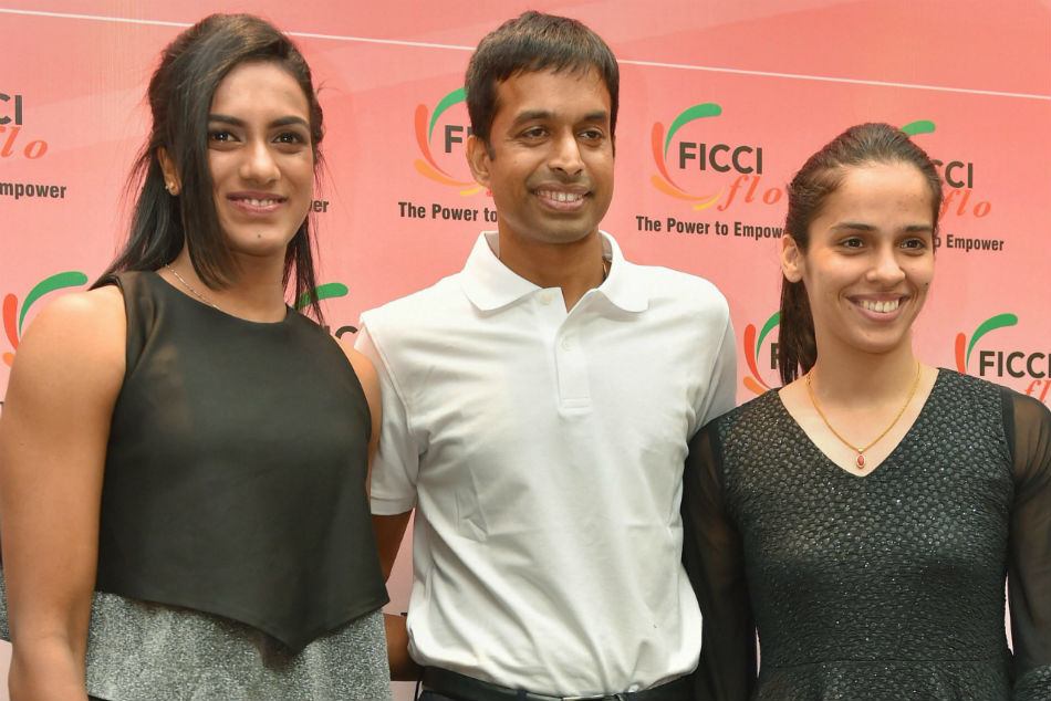 Shuttler Saina Nehwal and PV Sindhu with their coach P Gopichand during an interactive session organised by FICCI Ladies organisation (FLO), in New Delhi on Saturday.