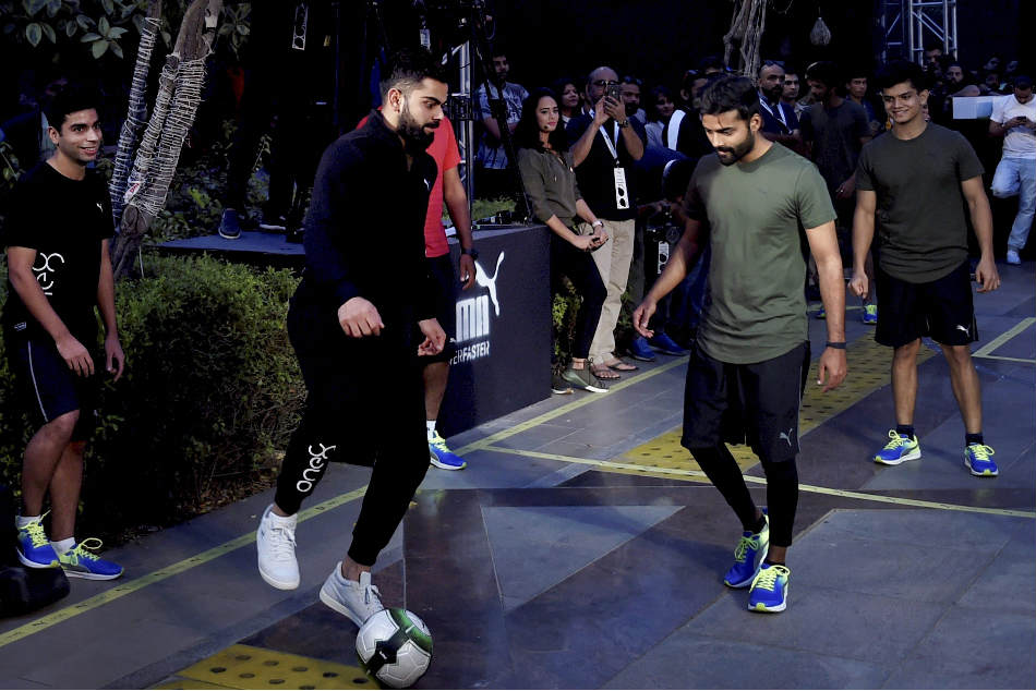 Virat Kohli playing football at a promotional event