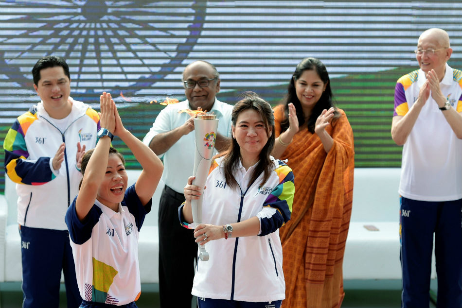 Susi Susanti holds the torch before handing over to Mary Kom