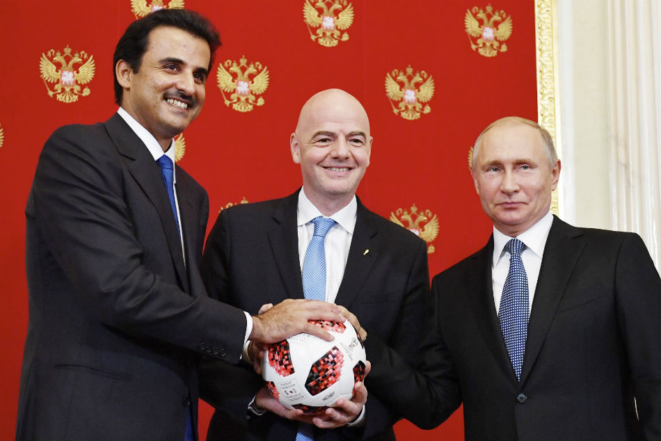 Gianni Infantino is flanked by Sheikh Tamim bin Hamad Al Thani, left, and Vladimir Putin at the handover ceremony