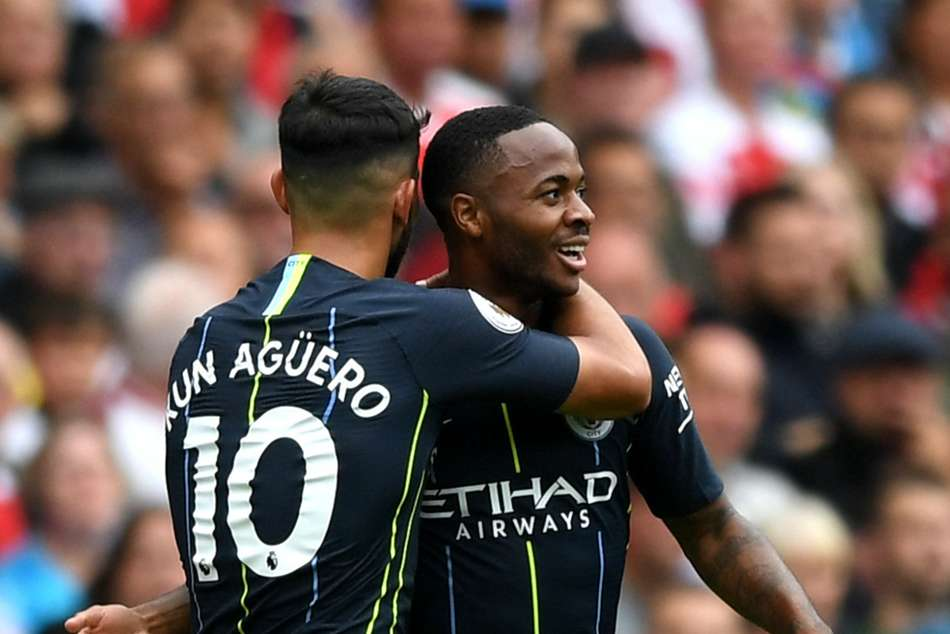 Raheem Sterling of Manchester City celebrates with teammate Sergio Aguero after scoring against Arsenal on Sunday