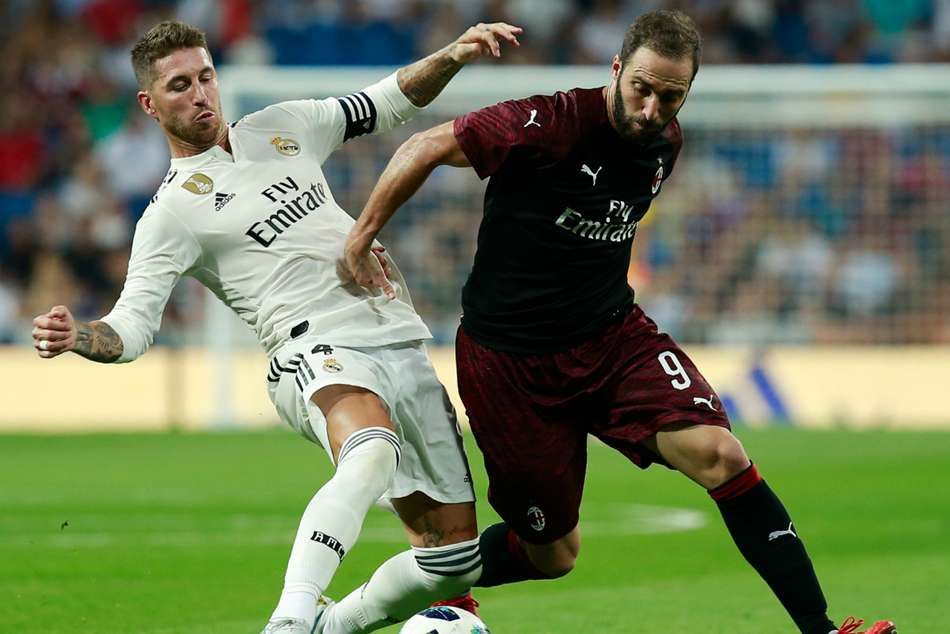 Real Madrids Sergio Ramos (left) fights for the ball with Milans Gonzalo Higuain
