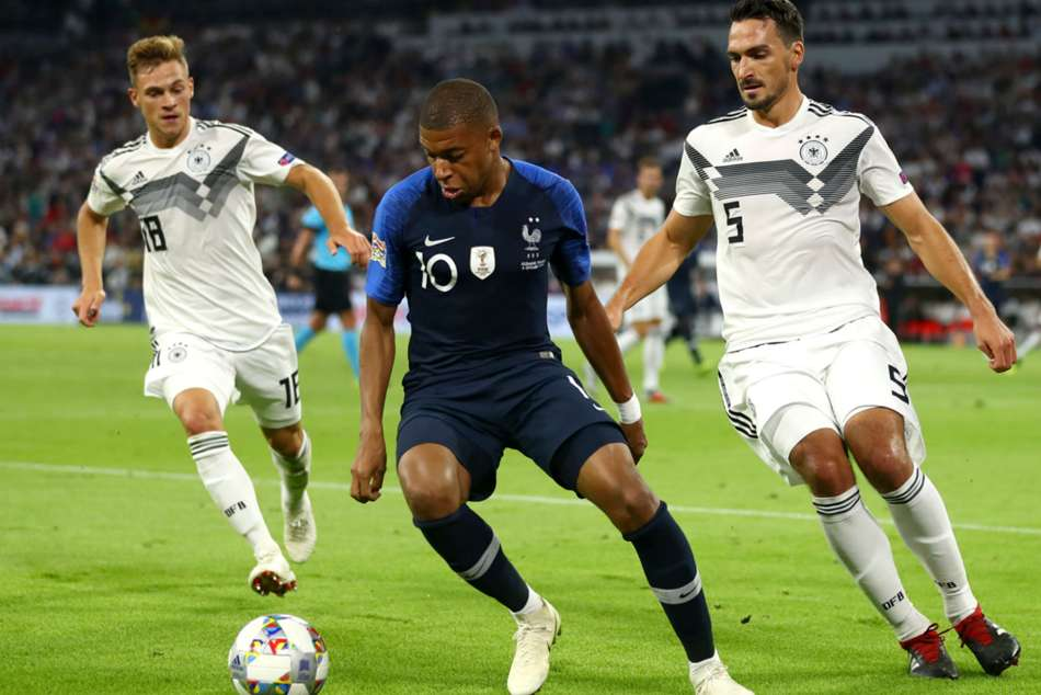 Frances Kylian Mbappe (centre) dribbles past Germanys Mats Hummels (right) and Joshu Kimmich