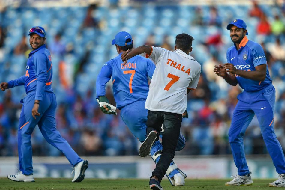 Fan breaks security for embrace from Dhoni